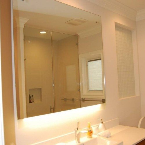 Backlit Frameless Vanity Mirror Set with Standoffs and Caps in Bathroom | Mirrors Gallery | Anchor-Ventana Glass